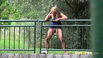 Pretty Blonde Pisses Through Railings