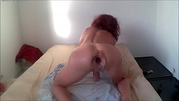 crossdresser playing with a large tunnel butt plug