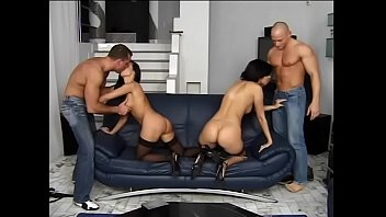 Two dudes fuck hard in all holes of two gorgeous whores in black stockings on the couch in the living room