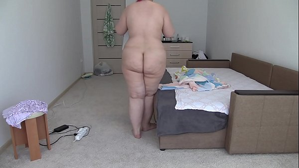 A hidden camera peeps behind a naked BBW with a...
