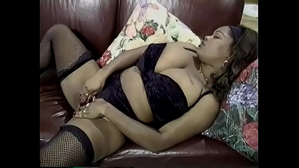 Horny black babe Kim Eternity spreads her pussy and licks her tits on sofa