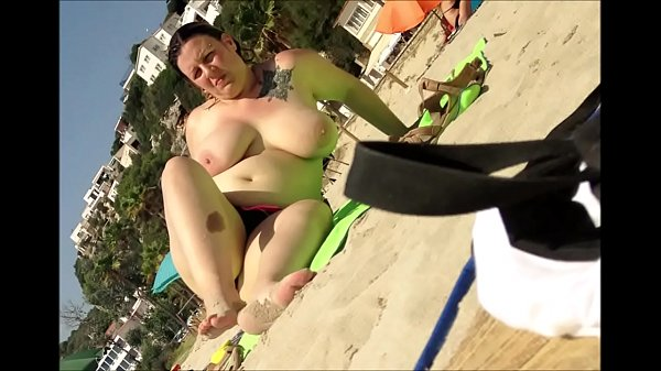 Voyeur films a topless woman with huge boobs on the beach