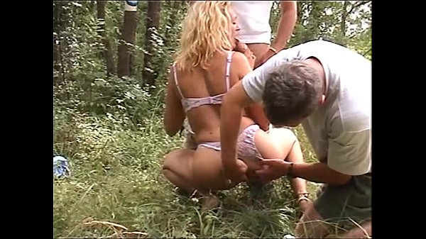 Blonde whore pissing in the wood fucked by two farmers