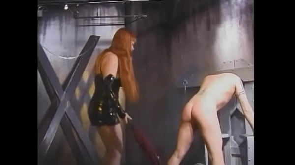 Two red-haired furies in latex dresses hang clothespins on the body of a young guy and spank him with a whip Thumb