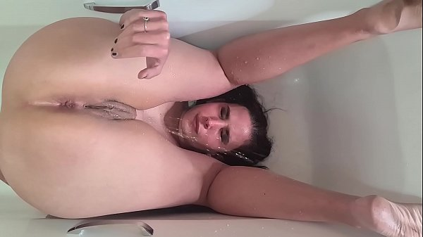 Piss whore pissing over her face in the bathtub