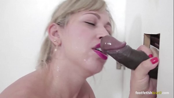 Mirella Mansur at gloryhole playing with a big black dick and doing footjob, sucking all and taking a huge cumshot in her mouth
