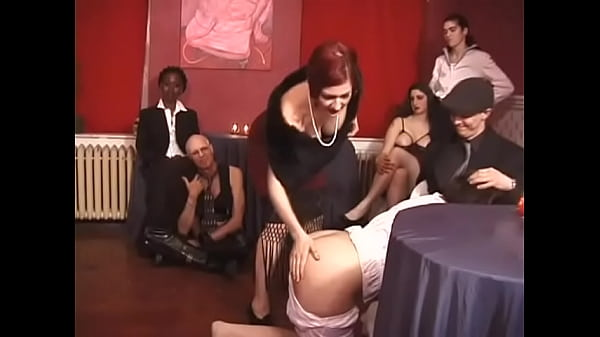A cute chick is spanked on an appetizing ass with whips by two impudent bitches in front of the guests of the party Thumb