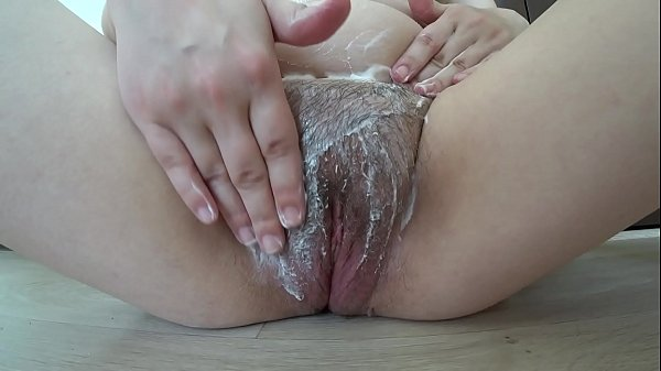 Hairy pussy masturbates with cream. A milf in early pregnancy smears the body with cream and fingering.