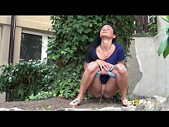 Public Pissing - Cute dark haired teen squats to pee in a garden