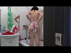 Brunette with a juicy ass in the bathroom is washed and masturbates with a stream of water and with a dildo.