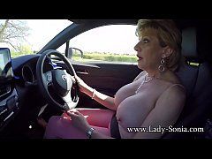 Mature British lady pulls her big tits out in the car
