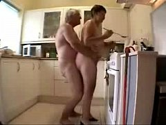 Old grand parents having fun in the kitchen. Am...