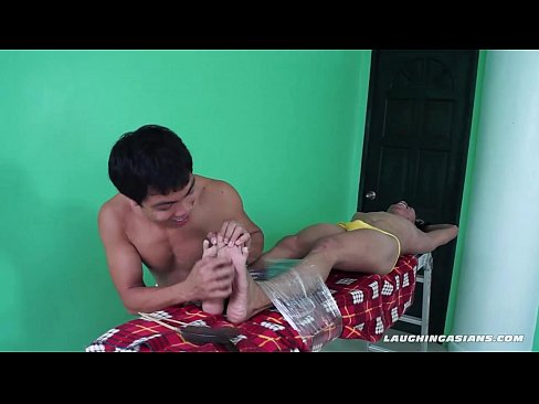 asian boy spreadeagled and tickled by two