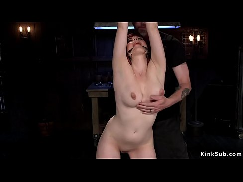Redhead newcomer Jessica Ryan in metal device bondage gets feet and ass caned then throat and pussy fucked with dick on a stick in dungeon
